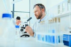 Молодые доктора в форме работая на испытательной лаборатории Стоковые Изображения RF