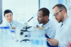 Молодые доктора в форме работая на испытательной лаборатории Стоковая Фотография RF