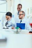 Молодые доктора в форме работая на испытательной лаборатории Стоковое фото RF