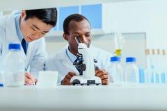 Молодые доктора в форме работая на испытательной лаборатории Стоковые Изображения