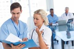 Молодые доктора говоря о голубом файле Стоковое Фото
