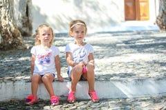 Молодые очаровательные девушки сидя на улице в старой Стоковые Изображения RF