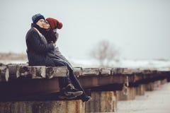 Молодые парень и девушка в носке зимы, объятии и наслаждаются пейзажем зимы стоковое фото