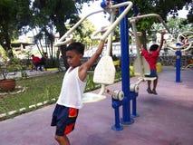 Молодые парни играют на внешнем парке с оборудованиями спортзала Стоковое Изображение