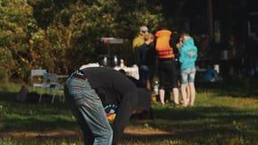 Молодые парни кладут дальше гигантские ботинки для того чтобы участвовать в конкуренции масленицы в парк акции видеоматериалы