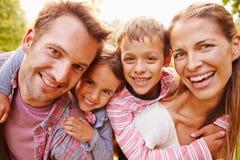 Молодые парни обнимая родителей outdoors, близко вверх по портрету Стоковое Изображение