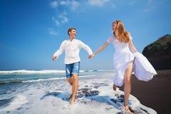 Молодые пары бегут пляжем отработанной формовочной смеси вдоль прибоя моря Стоковая Фотография