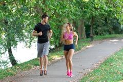 Молодые пары бежать в раннем утре на парке стоковые изображения