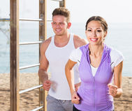 Молодые пары бежать на пляже морским путем Стоковое Изображение