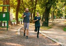 Молодые пары бежать на jogging следе через лес Стоковое Фото