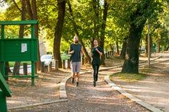 Молодые пары бежать на jogging следе через лес Стоковые Изображения