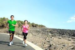 Молодые пары бежать совместно на jogging следе Стоковые Фотографии RF
