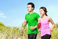 Молодые пары бежать совместно стоковые фото