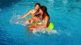 Молодые пары брызгая и имея потеху в бассейне сток-видео