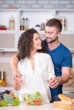 Молодые пары варя обедающий совместно в кухне стоковое фото