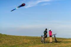 Молодые пары велосипедистов восхищают змеев большого летания multi покрашенные на парке восточного побережья стоковое фото