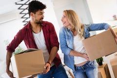 Молодые пары двигая в новый дом и распаковывая коробки carboard Стоковое Изображение