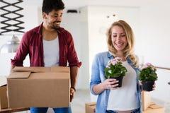 Молодые пары двигая в новый дом и распаковывая коробки carboard Стоковая Фотография RF