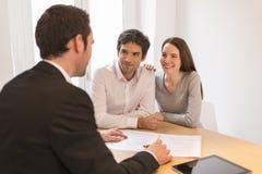 Молодые пары встречая недвижимый агент для того чтобы купить свойство стоковое изображение