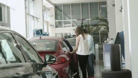 Молодые пары выбирают современный автомобиль в автосалоне видеоматериал