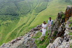 Молодые пары в влюбленности, наслаждаясь их отключением в горах Взгляд со стороны с большими красивыми горами на переднем плане Стоковые Фотографии RF