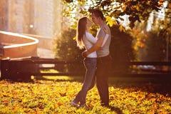 Молодые пары в влюбленности, обнимая на заходе солнца в парке Стоковое фото RF