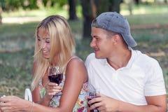 Молодые пары в влюбленности ослабляют в природе пока выпивающ вино стоковые фото