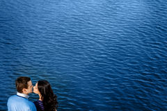 Молодые пары в влюбленности ослабляя на террасе около воды Стоковое Изображение RF