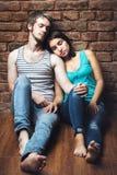 Молодые пары в влюбленности сидя на поле Стоковые Фотографии RF