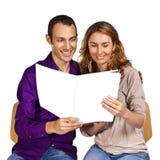 Молодые пары в влюбленности читая совместно брошюру Стоковое Изображение