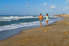 Молодые пары в их двадчадках jogging на песочном Стоковые Фото