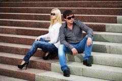 Молодые пары в конфликте сидя на шагах Стоковые Фотографии RF