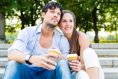Молодые пары в кофе парка города выпивая Стоковые Фотографии RF