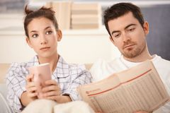 Молодые пары в кровати укомплектовывают личным составом пробуренную женщину чтения стоковые изображения rf