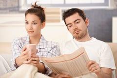 Молодые пары в кровати укомплектовывают личным составом чай женщины чтения выпивая Стоковые Изображения RF