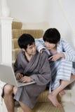 Молодые пары в купальном халате сидя на лестнице с компьтер-книжкой Стоковые Изображения