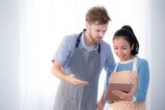 Молодые пары в кухне смотря таблетку Стоковая Фотография