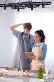 Молодые пары в кухне смотря таблетку Стоковое Фото