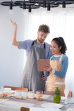Молодые пары в кухне смотря таблетку Стоковые Изображения RF