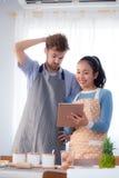 Молодые пары в кухне смотря таблетку Стоковые Изображения