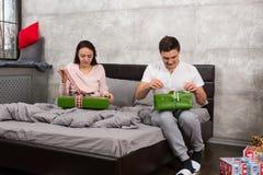 Молодые пары в пижамах распаковывая их настоящие моменты пока сидящ дальше Стоковые Фотографии RF