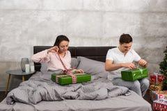 Молодые пары в пижамах распаковывая их настоящие моменты пока сидящ o Стоковые Изображения