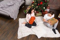 Молодые пары в пижамах распаковывая их настоящие моменты пока сидящ o Стоковое фото RF