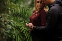 Молодые пары в саде не смотря в камере Стоковые Изображения RF