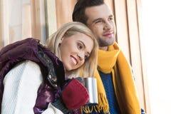 Молодые пары в теплых одеждах обнимая и смотря прочь на крылечке Стоковая Фотография RF