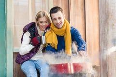 Молодые пары в теплых одеждах сидя совместно около гриля на крылечке Стоковая Фотография RF