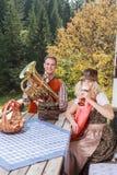 Молодые пары в традиционных баварских одеждах наслаждаются вашим отдыхом в общем Стоковое Фото