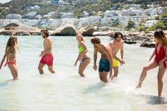 Молодые пары в beachwear наслаждаясь в море Стоковые Изображения RF