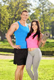 Молодые пары в sportswear представляя в парке Стоковое фото RF