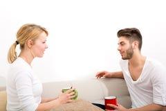 Молодые пары говоря на софе Стоковые Фотографии RF